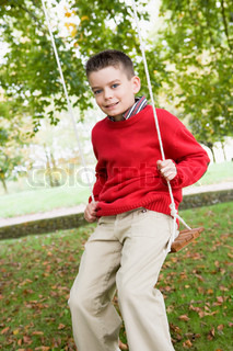Young boy playing oon tree swing in garden