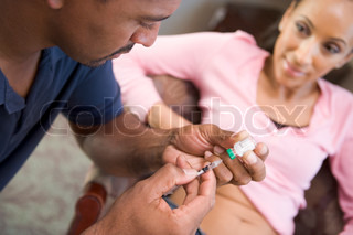 Man helping woman inject drugs to achieve pregnancy at home