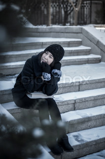 Happy young woman sitting on snow step