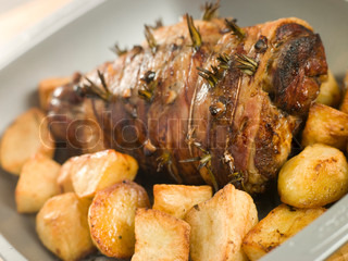 Roasting tin of Roast Leg of Lamb Studded with Garlic and Rosemary and Roast Potatoes
