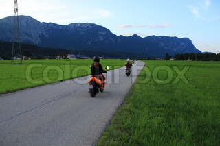 The girlfriends on the scooters ride over the street and go home in the summer in Austria.