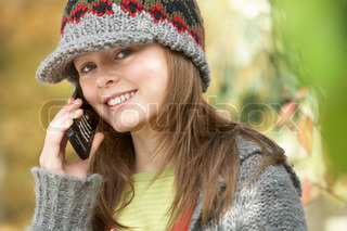 Head And Shoulders Of Young Girl In Autumn Woodland Using Mobile Phone