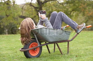 Young Girl Laying Wheelbarrow Using Smart Mobile Phone