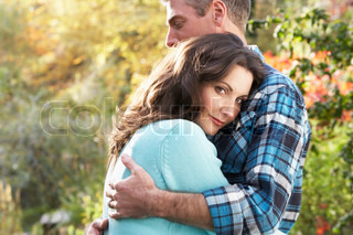 Close Up Of Romantic Couple Embracing By Autumn Woodland