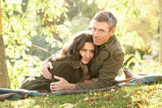 Romantic Couple Relaxing Outdoors In Autumn Landscape
