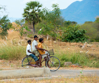 TRICHY, INDIA - FEBRUARY 15: An unidentified three teenage boy riding a bike on a rural road. India, Tamil Nadu, near Trichy. February 15, 2013