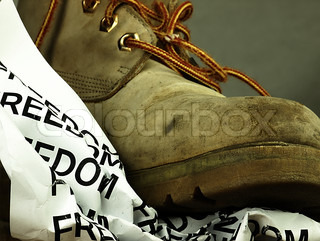 The word freedom crushed by a heavy, old military boot.