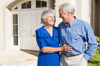 Senior couple standing outside front door of house