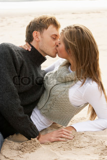 Portrait Of Romantic Young Couple Kissing On Beach