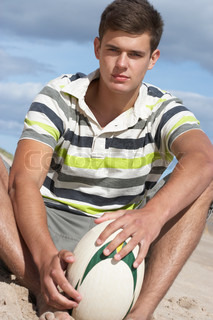 Teenage Boy Sitting On Beach Holding Rugby Ball