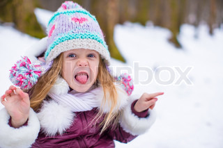Portrait of funny little girl outdoors on warm winter day