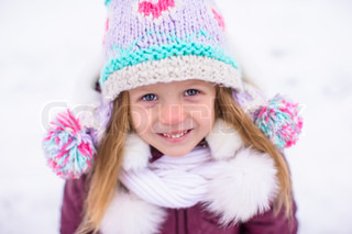 Adorable little happy girl have fun in winter snowy day outdoor