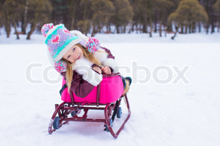 Adorable little happy girl sledding in winter snowy day