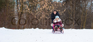 Little girl and happy father sledding in winter snowy day