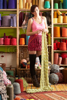 Young Woman Knitting Scarf Standing In Front Of Yarn Display