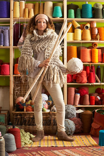 Woman Wearing Knitted Scarf Standing In Front Of Yarn Display Holding Giant Needles