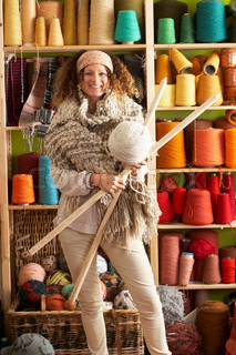 Woman Wearing Knitted Scarf Standing In Front Of Yarn Display Holding Giant Needles And Ball Of Wool