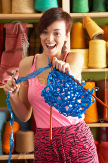 Young Woman Holding Knitting Standing In Front Of Yarn Display