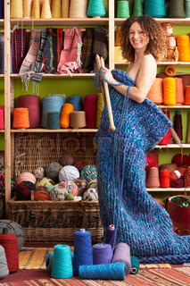 Naked Woman Standing In Knitted Item Standing In Front Of Yarn Display