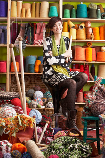 Young Woman Sitting On Stool Holding Knitting Needles In Front Of Yarn Display