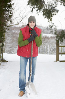 Young Man Clearing Snow From Drive