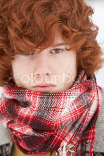 Teenage Boy Wearing Winter Clothes In Snowy Landscape