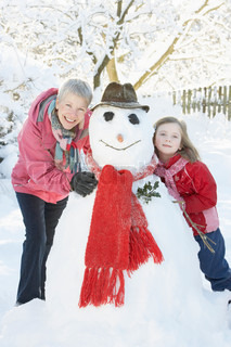 Young Girl With Grandmother Building Snowman In Garden