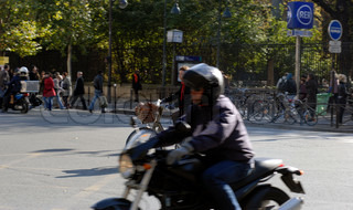 Motorbike and female cyclist in Paris traffic.