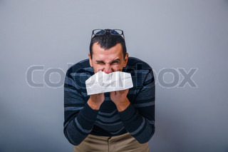 European-looking male of about thirty brunet blowing his nose in