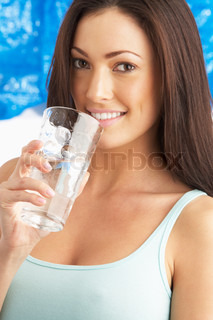 Young Woman Drinking Glass Of Water In Studio