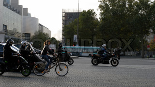 Woman on bicycle in Paris traffic among motorbikes and scooters.