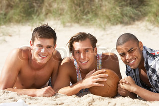 Three Young Men Relaxing On Beach With Football Together
