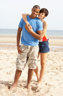 Romantic Young Couple Standing On Beach