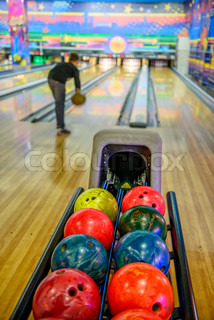 Bowling balls and player on blurred background