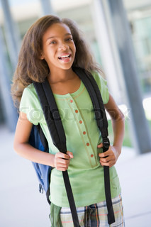 Elementary school pupil outside building with backpack