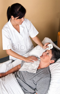 A nurse washes a patient
