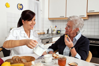 A geriatric nurse helping senior citizen at breakfast