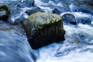 A creek with running water and stones (rocks)