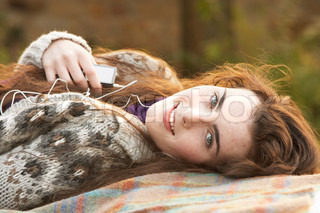 Portrait Of Beautiful Teenage Girl Outdoors Listening To MP3 Player In Autumn Landscape