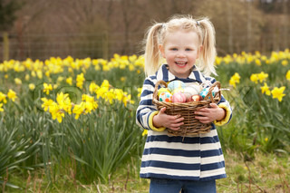 Young Girl Holding Basket von dekorierten Eier In Daffodil Field