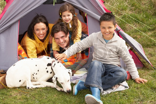 Young Family With Dog Relaxing Inside Tent On Camping Holiday