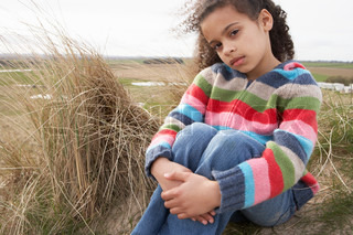 Young Girl Sitting Amongst Dunes On Winter Beach