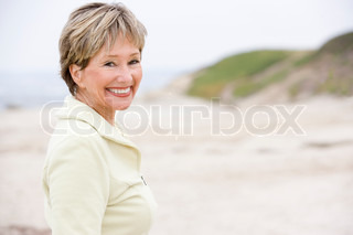 Smiling woman in her 60s standing on the beach