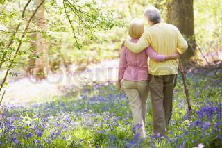 Et ældre ægtepar i skoven omgivet af lilla blomster og lys