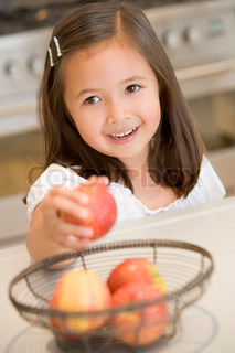 Girl taking apple from fruit basket at home