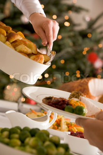 A woman serving roasted potatoes for Christmas dinner