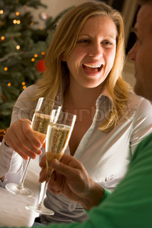 A caucasian man and woman toasting champagne on Christmas party