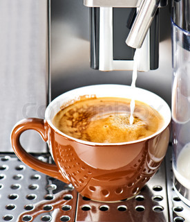 Coffee maker pouring fresh milk coffee in a cup