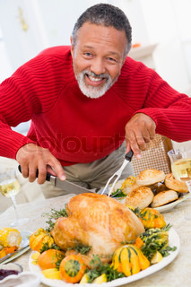 An african-american grandfather curving the turkey on Thanksgiving dinner
