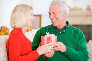An elderly couple in love exchanging gifts on Christmas day